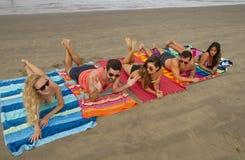 小组在海滩的年轻成人 免版税库存图片
