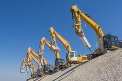小组在石渣小山的挖掘机 免版税库存图片