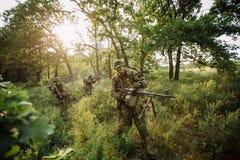 小组在袭击期间的战士特种部队在森林里 免版税库存图片