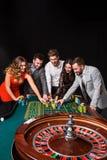 小组在轮盘赌桌后的青年人在黑背景 免版税库存图片