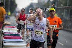 小组在运行在马拉松期间的街道的赛跑者 免版税库存图片