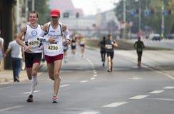 小组在运行在马拉松期间的街道的赛跑者 库存照片