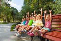 小组在长凳欢呼的举的手上的孩子 库存图片