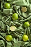 小组在绿色缎的整个和裁减新鲜的石灰 免版税图库摄影