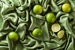 小组在绿色缎的整个和裁减新鲜的石灰 免版税库存照片