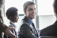 小组坐和微笑在业务会议上的商人 库存图片