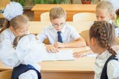 小组坐在书桌的学校教室的学童 免版税库存图片