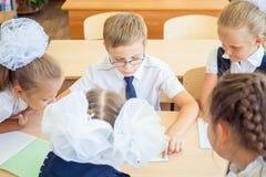 小组坐在书桌的学校教室的学童 免版税图库摄影