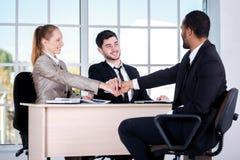 小组 坐在办公室的三个成功的商人和 免版税库存图片