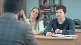 小组坐在他们的在观众席和等待的老师的书桌的大学生,当他谈话时 股票视频