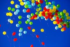 小组多彩多姿的氦气填装了在天空的气球 免版税库存图片