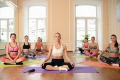 小组女孩实践在莲花坐的瑜伽 库存照片
