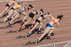 小组女孩运动员开始冲刺100米 免版税库存照片
