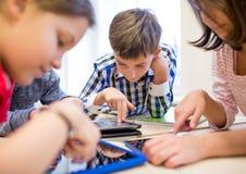 小组学校哄骗与片剂个人计算机在教室 免版税库存照片
