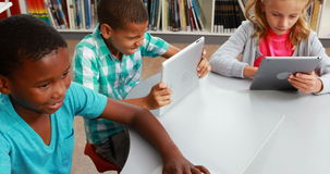 Group of school kids using digital tablet and laptop in library Stock Footage