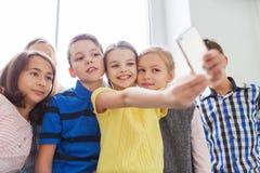 小组学校哄骗采取与智能手机的selfie 免版税库存照片