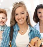小组学校走廊的愉快的学生女孩 免版税图库摄影