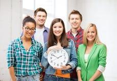 小组学生在有时钟的学校 图库摄影