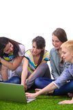 小组年轻学生坐绿草 图库摄影