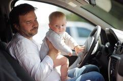 小婴孩和他的父亲获得乐趣在汽车 免版税库存照片