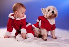 小婴孩在圣诞老人和狗在圣诞老人服装 免版税库存照片