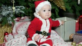 小婴孩在圣诞老人成套装备,逗人喜爱的男孩在家使用在圣诞树附近的,狂欢节服装戏剧的孩子穿戴了 影视素材