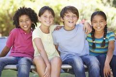 小组孩子一起坐绷床边缘  免版税库存照片
