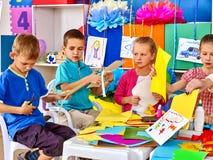 小组孩子做补花色纸在幼儿园 免版税库存照片
