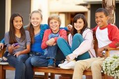 小组孩子坐在购物中心的长凳 库存照片