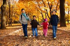 小组孩子步行在秋天公园 免版税库存照片