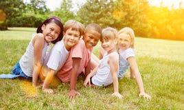 小组孩子获得乐趣在夏天在草甸 免版税库存照片