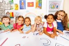 小组孩子,男孩和女孩读书的分类 免版税图库摄影