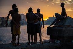 小组孩子从Malecon墙壁使用并且跳进H的大西洋 免版税库存照片
