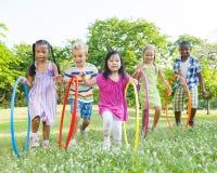 小组孩子Hula Hooping在公园 库存照片
