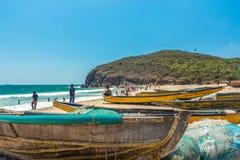 小组宽看法渔船在与人和峭壁在背景中,维沙卡帕特南, 2017年3月05日的海滨停放了 免版税库存图片