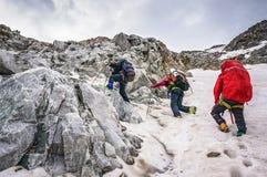 小组对山的登山人上升在一个复杂倾斜由岩石和雪组成 库存图片