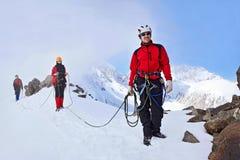 小组对山的登山人上升在一个复杂倾斜由岩石和雪组成 免版税图库摄影