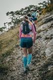 小组少妇运动员逐个攀登山 免版税库存图片