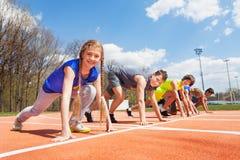小组少年赛跑者排队了准备好赛跑 免版税图库摄影