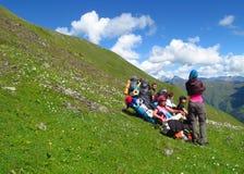小组登山人有休息在山绿色山谷 免版税图库摄影