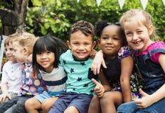 小组幼儿园哄骗朋友在坐和smilin附近武装 图库摄影