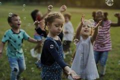 小组幼儿园哄骗演奏吹的泡影乐趣的朋友 免版税库存照片