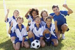 小组庆祝与战利品的足球队员的孩子 免版税库存图片
