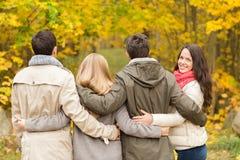 小组微笑的人和妇女在秋天停放 免版税库存照片