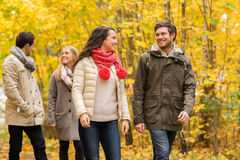 小组微笑的人和妇女在秋天停放 免版税库存图片