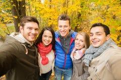 小组微笑的人和妇女在秋天停放 库存照片