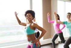 小组微笑的妇女跳舞在健身房或演播室 免版税图库摄影