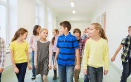 小组微笑的学校哄骗走在走廊 免版税库存照片