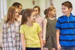 小组微笑的学校哄骗走在走廊 免版税图库摄影