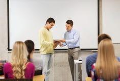 小组微笑的学生和老师在教室 免版税图库摄影